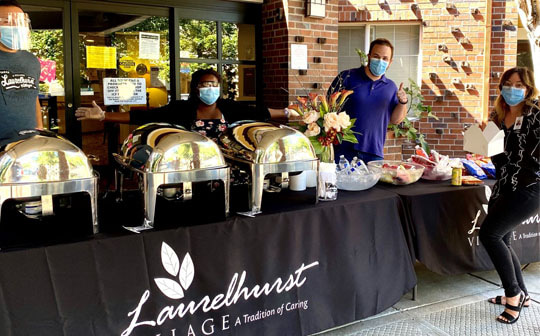 Masked employees from Avamere at Laurelhurst preparing a delicious looking buffet outside the front entrance
