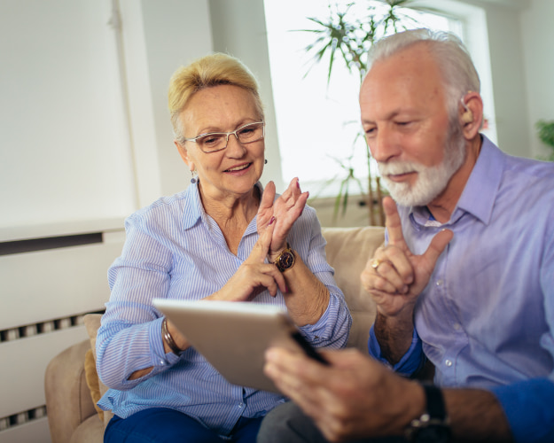 Couple viewing a tablet while using ASL