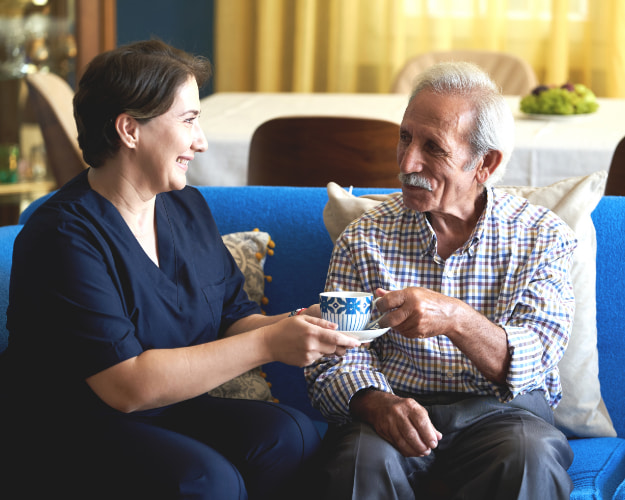 Caregiver handing a cup of tea on a saucer to an elderly gentleman