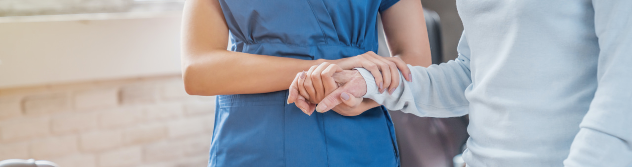 Nurse holding a patients hand and arm