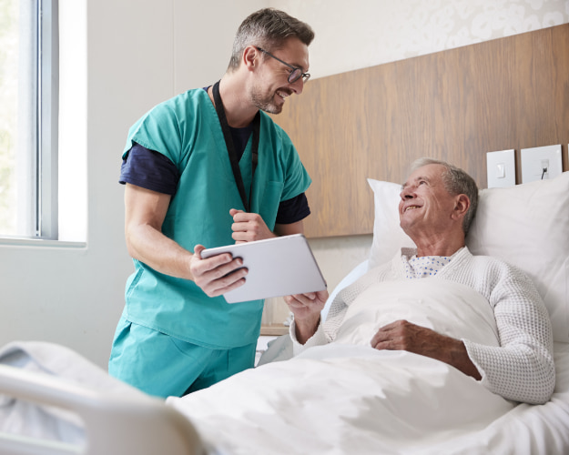 Cargiver showing a tablet to a patient