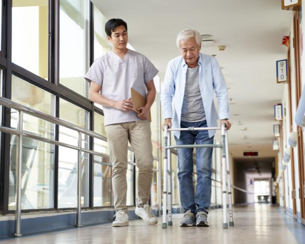 Caregiver walking next to an elderly man using a walker
