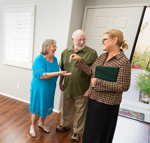 Woman handing keys for an apartment to an elderly couple