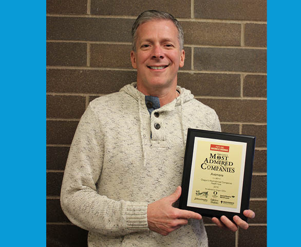 Bob Thomas, COO, poses with Avamere award from Portland Business Journal as one of Oregon's Most Admired Companies